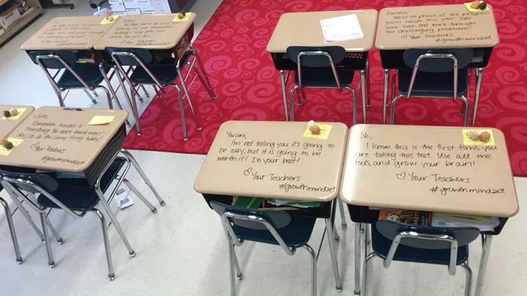 Teacher writes inspirational messages on student's desks on