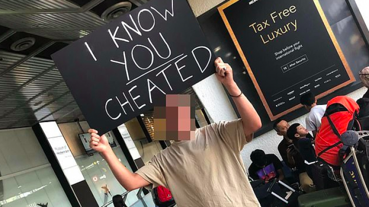 Man waits at airport with 'I know you cheated' sign for partner and holy mother of God