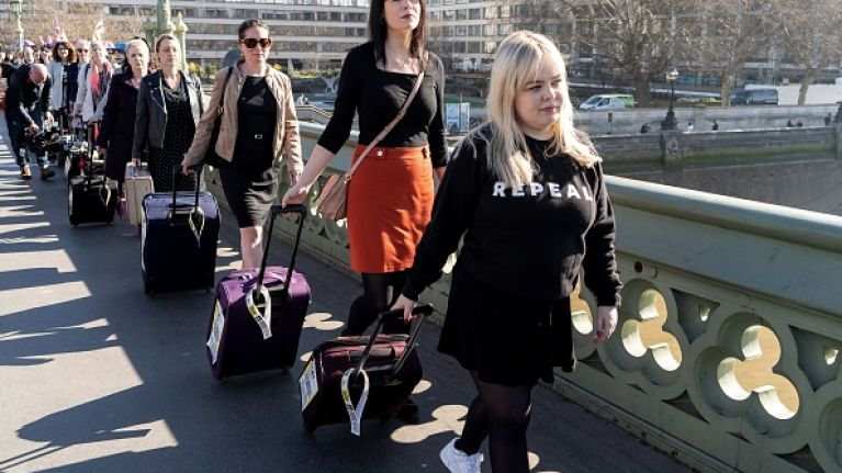 Women march with suitcases to protest against Northern Ireland's abortion laws