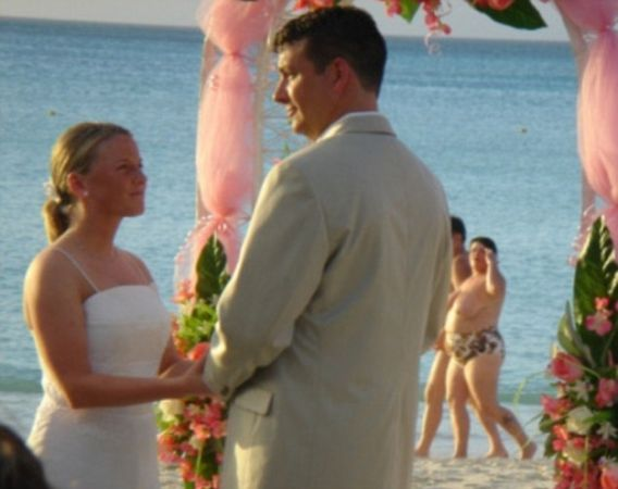 Wedding photobomb #10: This couple get an unwanted preview of what five years of marriage and a couple of kids will do to your bodies.