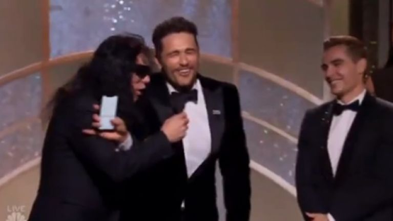 Tommy Wiseau tries to grab the microphone after James Franco's win