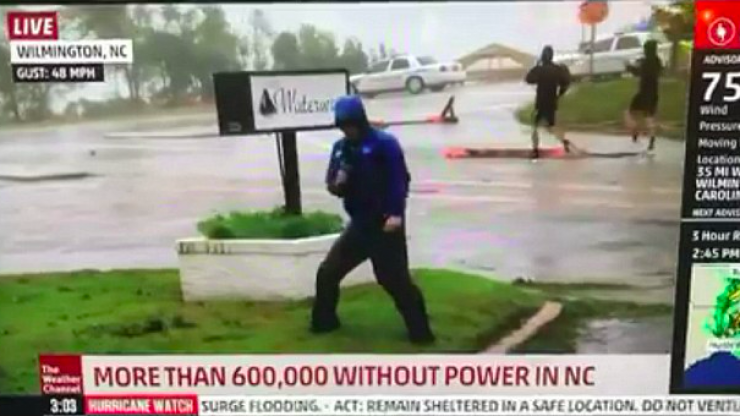 Weatherman called out for being 'dramatic' when men casually stroll past during Hurricane broadcast