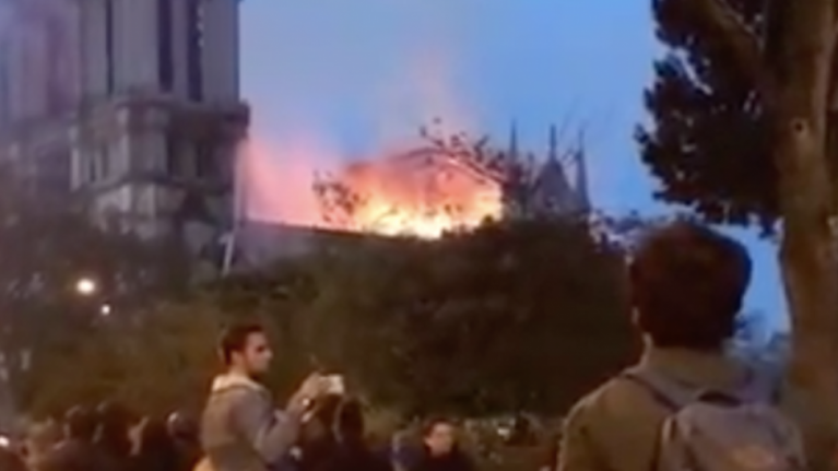 Watch Parisians sing at the feet of their burning Lady