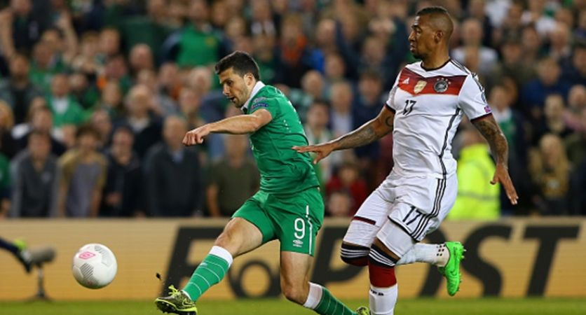 DUBLIN, IRELAND - OCTOBER 08:  Shane Long of Republic of Ireland scores the opening goal under pressure from Jerome Boateng of Germany uring the UEFA EURO 2016 Qualifier group D match between Republic of Ireland and Germany at the Aviva Stadium on October 8, 2015 in Dublin, Ireland.  (Photo by Alexander Hassenstein/Bongarts/Getty Images)