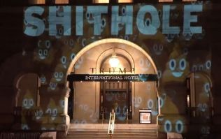 The word 'Shithole' is being projected on to the front of Donald Trump's hotel in Washington