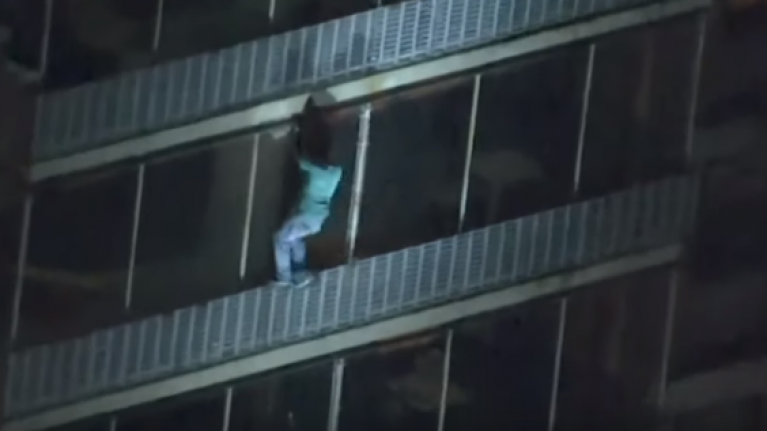 WATCH: Man scales down the side of a building as it catches fire
